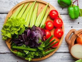 Fresh vegetables cucumber, tomato, onion, pepper on wooden cutting board
